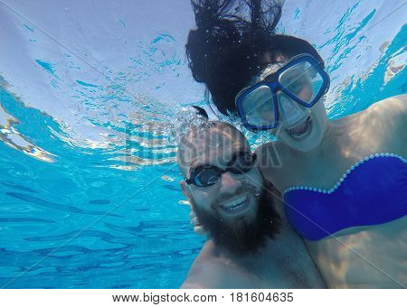 The Guy And The Girl Are Swimming Under The Water