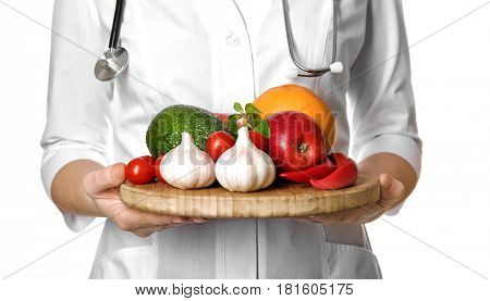 Doctor holding wooden board with heart healthy foods on white background