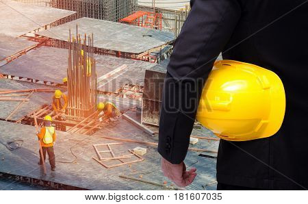 back view of smart businessman in black suit with yellow safety helmet on background of construction workers working at construction site with sunlight effect.
