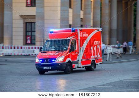 BERLIN GERMANY - MAY 22 2014: Mercedes-Benz Sprinter firetruck speeding to an emergency near Brandenburger Gate in Berlin Germany.