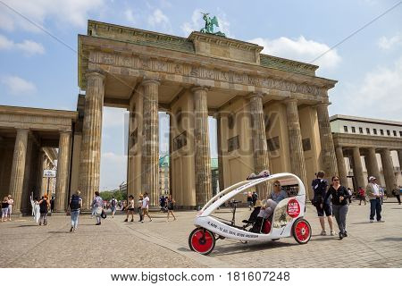 BERLIN GERMANY - MAY 23 2014: Taxi bike waiting in front of the Brandenburg Gate in Berlin Germany. A total of 5334 kilometres of roads run through the city of Berlin.