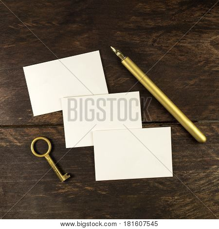 An overhead photo of blank white thick cardboard business cards on a dark wooden background texture with a golden ink pen and a vintage key. A square mockup or a minimalist banner with copy space