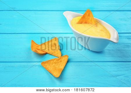 Gravy boat with tasty cheese sauce and snack on color wooden background