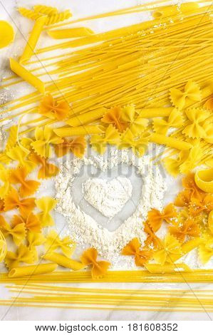 Various types of pasta on a white marble table, with a heart drawn in flour