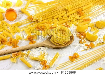 Various types of pasta on a white marble table with flour and an egg, with a wooden ladle