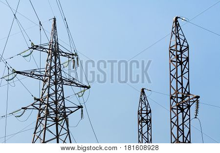 Three power transmission towers. High voltage. Blue background.