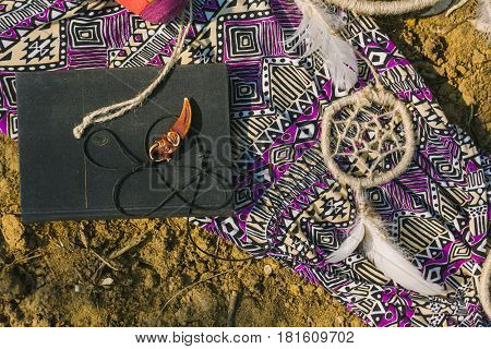 dress dreamcatcher and book lying on dry land. hipster style