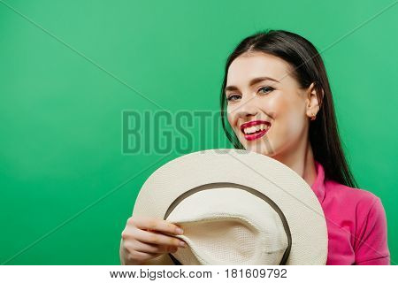 Closeup Portrait of Pretty Brunette with Long Hair Posing in Cowboy Hat and Bright Pink Shirt on Green Background. Joyous Toothy Smiling Girl with Professional Makeup in Studio.