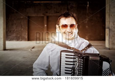 Portrait of the musician playing the harmonica, accordion in the dark hall