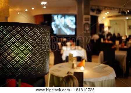 Lampshade and people sitting in restaurant, at evening, focus on lamp