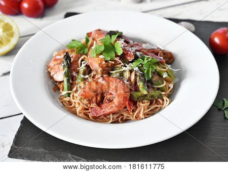 Delicious pasta with great shrimps or prawns and green asparagus on a white plate. Healthy food on a white table or planks. Spaghetti frutti di mare.