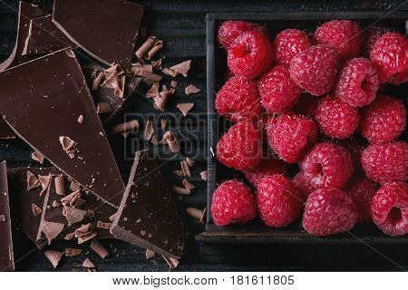 Dark and milk chopping chocolate and chips with fresh raspberries in black wood box over black burnt wooden background. Top view, close up. Chocolate dessert concept