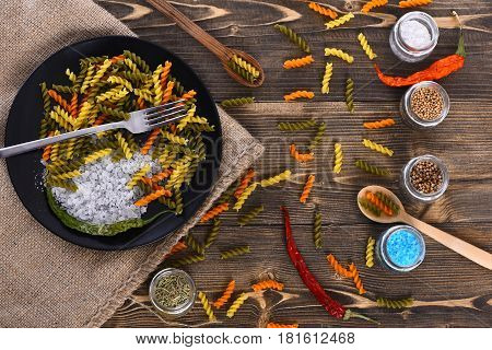 Colorful Dried Fusilli, Salt Crystals And Fork In Black Bowl