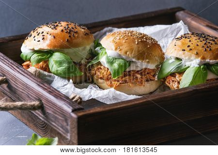 Homemade mini burgers with pulled chicken, basil, mozzarella cheese and yogurt sauce on wooden tray with baking paper over gray texture background. Healthy fast food concept