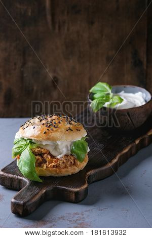 Homemade mini burger with pulled chicken, basil, mozzarella cheese and yogurt sauce on wooden serving board over gray texture background. Healthy fast food concept