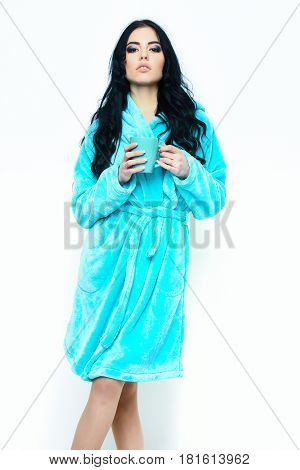 pretty serious cute sexy girl or beautiful woman with fashion makeup and curly long hair posing in turquoise velour bathrobe with cup isolated on white background