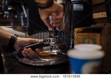 coffee grinder in the coffee shop. Barista grinding fresh coffee into bayonet