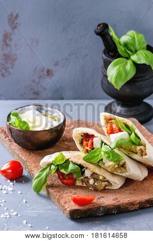 Pita bread sandwiches with grilled vegetables paprika, eggplant, tomato, basil and feta cheese served on terracotta board with yogurt sauce over gray stone background. Healthy fast food concept.