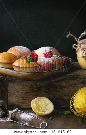Homemade lemon muffin cupcakes with fresh raspberries, sugar powder, mint, served with jar of lemon curd and lemons on wooden box over dark background. Dark rustic style.