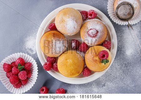 Homemade lemon muffin cupcakes with fresh raspberries, sugar powder, mint, served with vintage sieve over gray blue texture stone background. Top view with space.