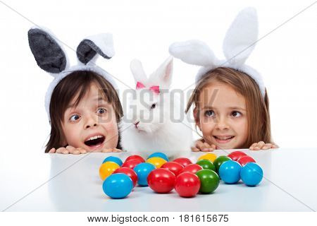 Kids happy to find the easter bunny and lots of colorful eggs - focus on the rabbit