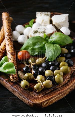 Mediterranean appetizer antipasti board with green black olives, feta cheese, mozzarella, capers, pepper, basil with grissini bread sticks over black wood burnt background. Close up
