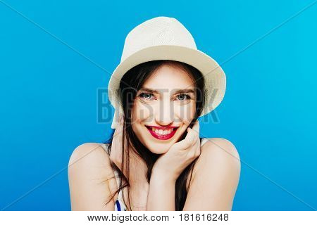 Portrait of Joyous Female Model in Summer Hat Posing in Studio on Blue Background. Vacation Concept.