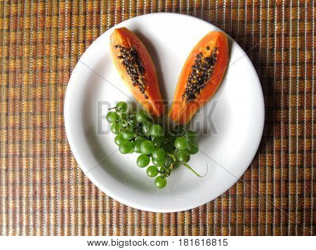 Two slices of papaya placed on white plate together with grapes
