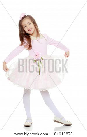 Dressy little girl long blonde hair, beautiful pink dress and a rose in her hair.It stretches over the edges of the dress.Isolated on white background.