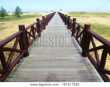 Wooden bridge leading to sea shore with sea in background