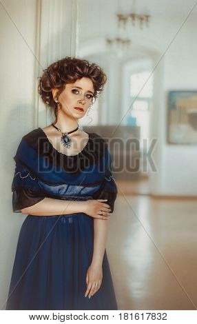 Young beautiful luxurious woman in long elegant dress .Beautiful young woman in a luxurious classic interior. Seductive brunette woman in luxury manor vintage style