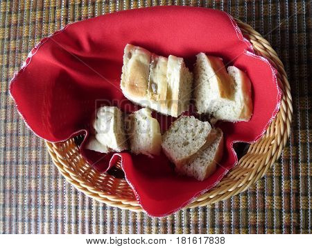 Homemade bread on basket and red tablecloth