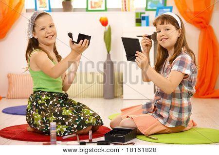 Junge Mädchen spielen mit Make-up zusammen zu Hause, am Boden sitzen.?