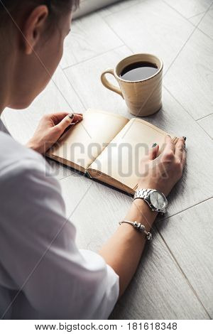 Stylish girl reading a book lying on the floor. Clock. A bracelet. Education, Fashion, Lifestyle and