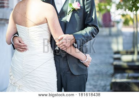 Unrecognizable cut out of the bride and groom enjoying eachother during the photoshoot on their wedding day