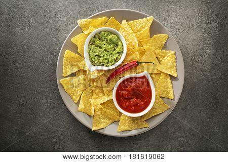 Guacamole and tomato salsa with corn nachos chips