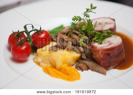 Very tasteful dinner in a restaurant with cherry tomatoes meat mashed potatoes and mushrooms