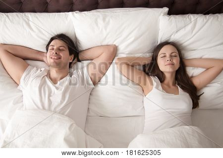 Young Happy married couple wearing white resting with eyes closed in bed, lying with hands behind the head after waking up in the morning, or going to sleep at night. Lovers relaxing in bed. Top view