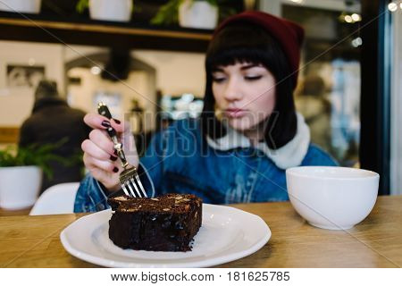 Young hipster girl eating a delicious chocolate cake in the beautiful cafe
