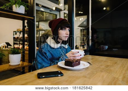 Young hipster girl eats tasty chocolate cake and drinking a hot drink in a nice cafe