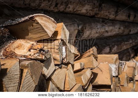 Natural wooden background, closeup of chopped firewood. Firewood stacked and prepared for winter Pile of wood logs. Chopped firewood on a stack.