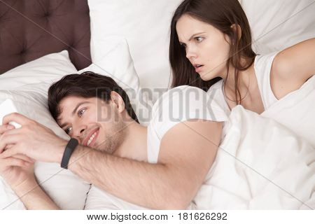 Shocked woman noticing her husband checking his smartphone and texting his lover while lying next to his wife in bed. Surprised lady caught her man cheating on mobile, chatting with his mistress