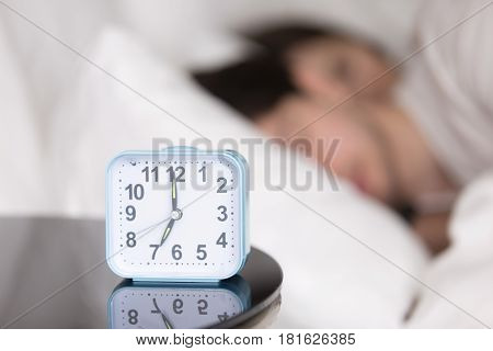 Man and woman quietly sleeping together on white bed early in the morning at home. Focus on alarm clock on nightstand near the bed with couple asleep in the background