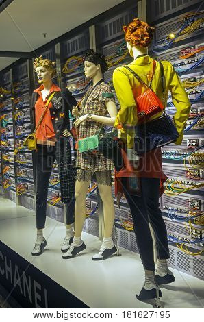 PARIS FRANCE - MARCH 27 2017: Installation in the showcase of the Printemps department store in Paris France. Fashion and high technology - elegant mannequins on the background of computer servers.