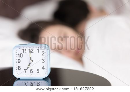 Alarm clock standing on the table telling time few seconds before ringing to wake up young sleeping couple still resting in bed in the background. Wake up in the morning, daily regimen, workdays