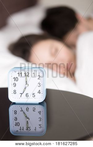Before waking up on weekdays. Vertical view of alarm clock on the table and lovely young couple on background sleeping in bed. Focus on clock, telling early hour, earliness, daily alarm