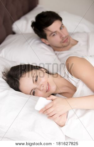 Smiling dreamy wife relaxing in bed looking at mobile phone hiding something from suspicious husband lying next to her. Jealous man controlling her, thinking his girlfriend having an affair, cheating