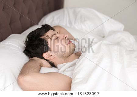 Relaxed guy lying up in comfortable cozy bed wearing white t-shirt, sleeping or napping with eyes closed, holding hands behind the head, resting after working day or waking up in the morning poster