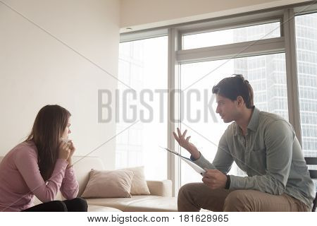 Young lady crying, holding a handkerchief sitting on the couch while consulting by male psychologist. Therapist talking to sad depressed woman in tears, helping her to find the answers