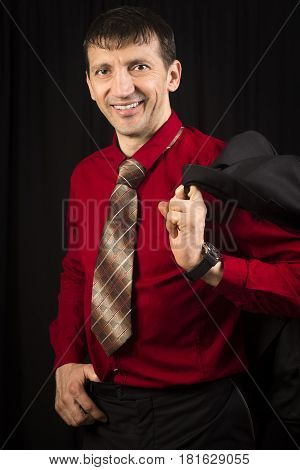 Elegant handsome smiling man is posing in red shirt and necktie on black background.